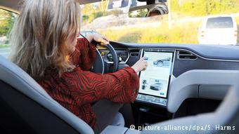 Женщина за рулем управляет компьютером электромобиля Tesla S